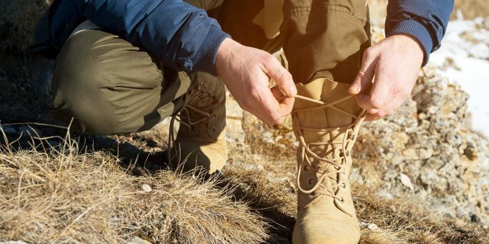 A close-up of a traveler in the mountains in the winter tying shoelaces on his shoes. The concept of mountain tourism and trekking in sports and tourism